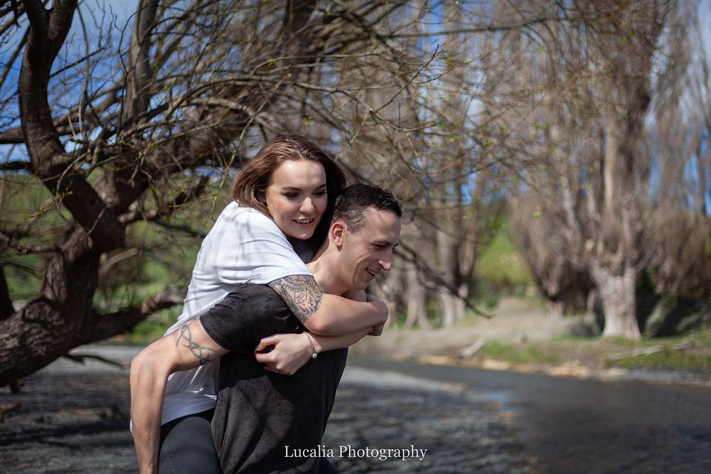 bride-to-be being piggybacked by her fiancé near a river, Wairarapa wedding photographer