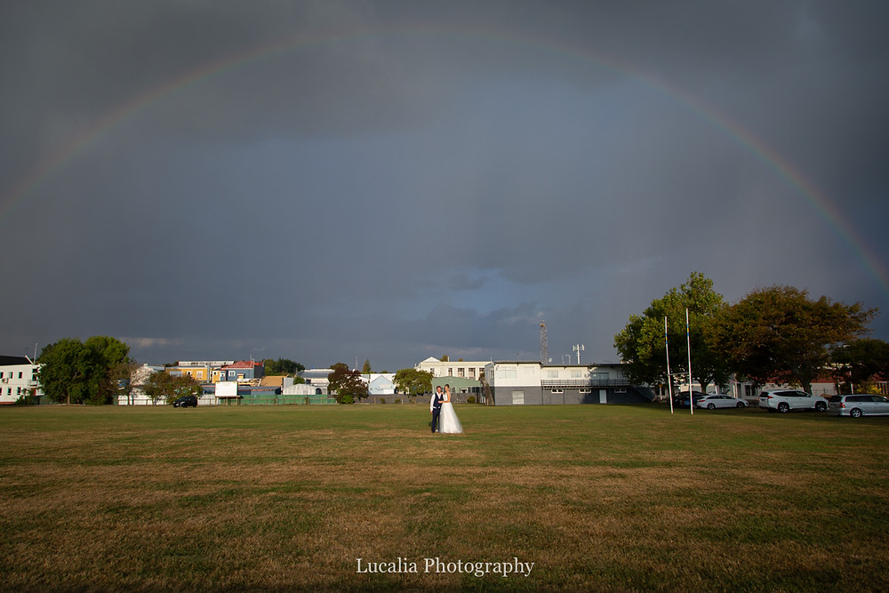 wedding couple standing underneath a rainbow, Wairarapa
