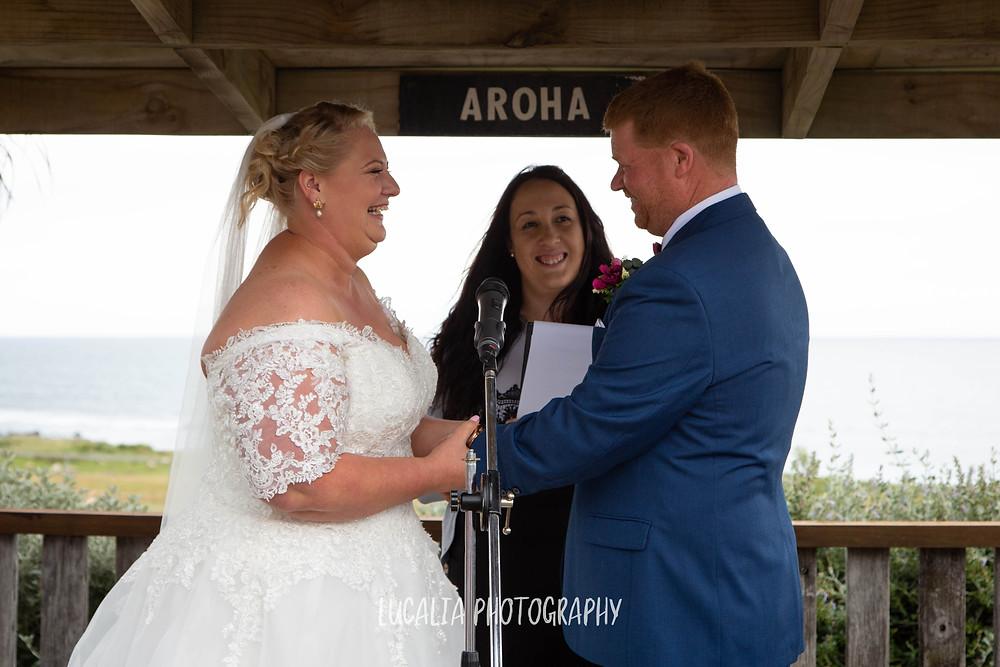 bride and groom laughing during wedding ceremony, Emma Ayling Wairarapa wedding celebrant, Waimeha Camping Village, Ngawi, Wairarapa wedding