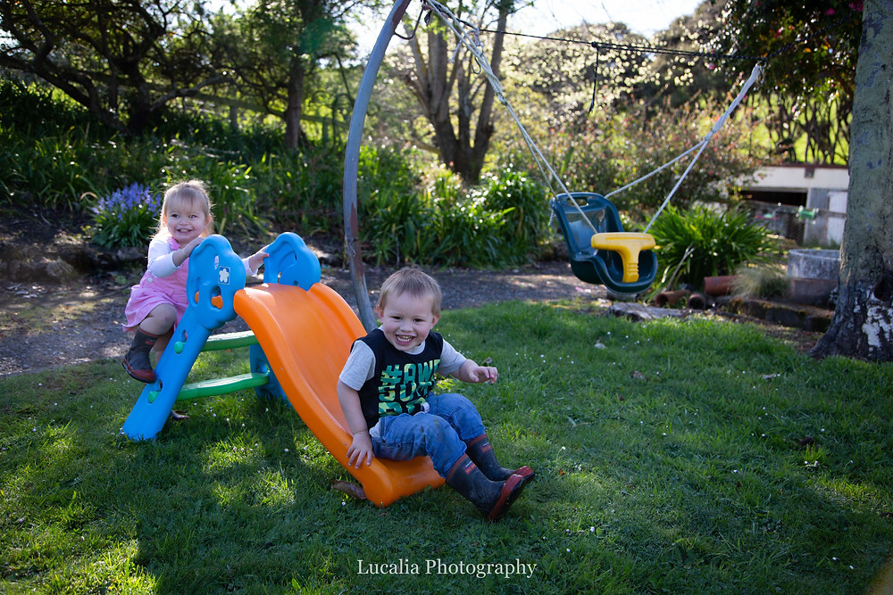 two toddlers playing on a slide smiling, Wairarapa family photographer