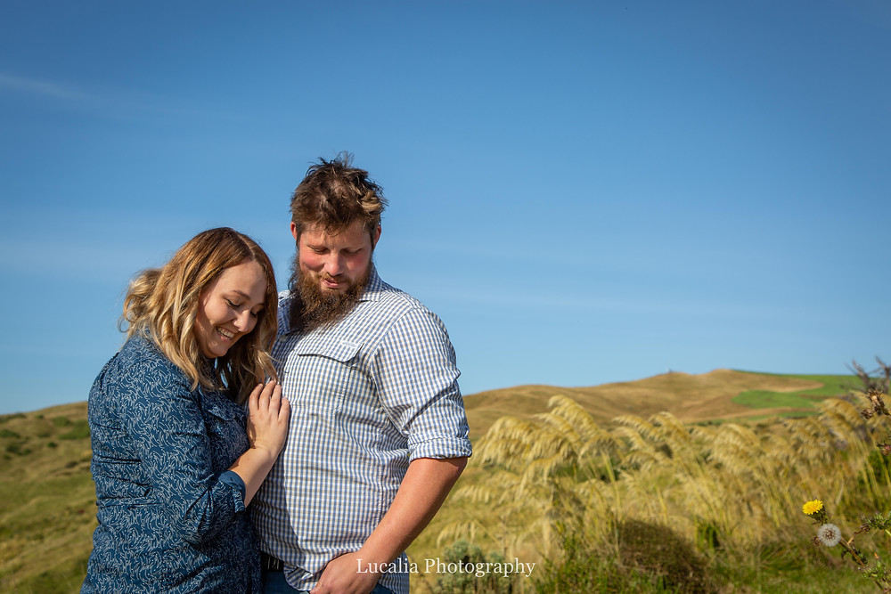 engaged couple looking down, blue sky day Castlepoint Wairarapa