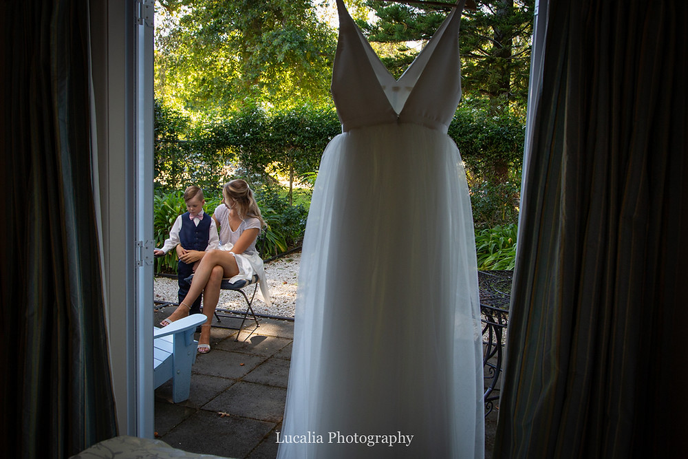 bride talks to her son with wedding dress hanging up, Wairarapa wedding photographer