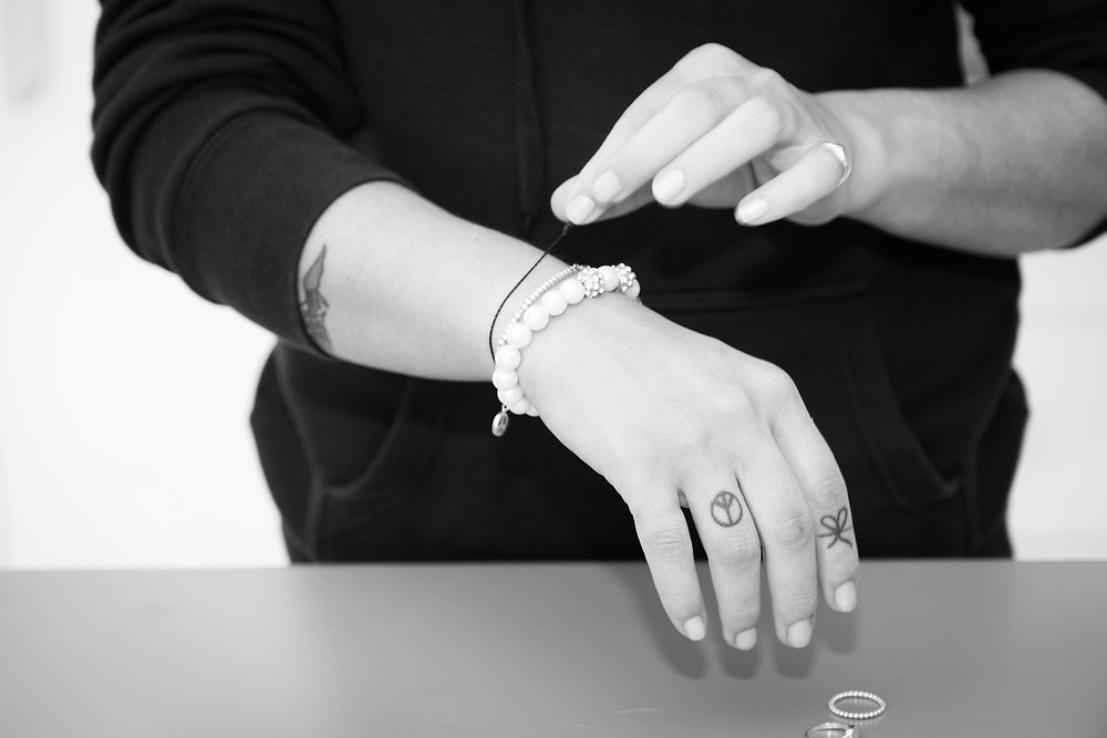 black and white photos of a bridesmaid with tattoos removing her jewellery