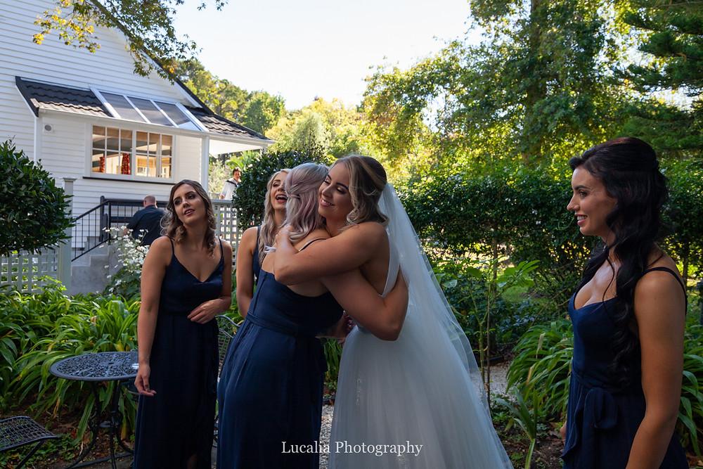 bride hugging bridesmaids, Wairarapa