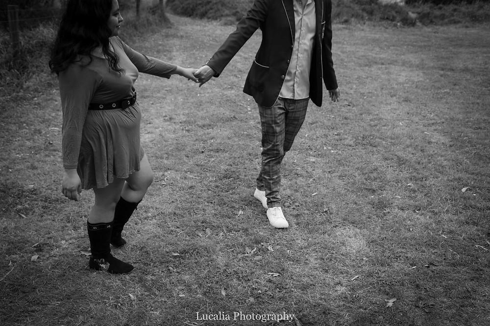 engaged couple holding hands walking on grass, Wairarapa