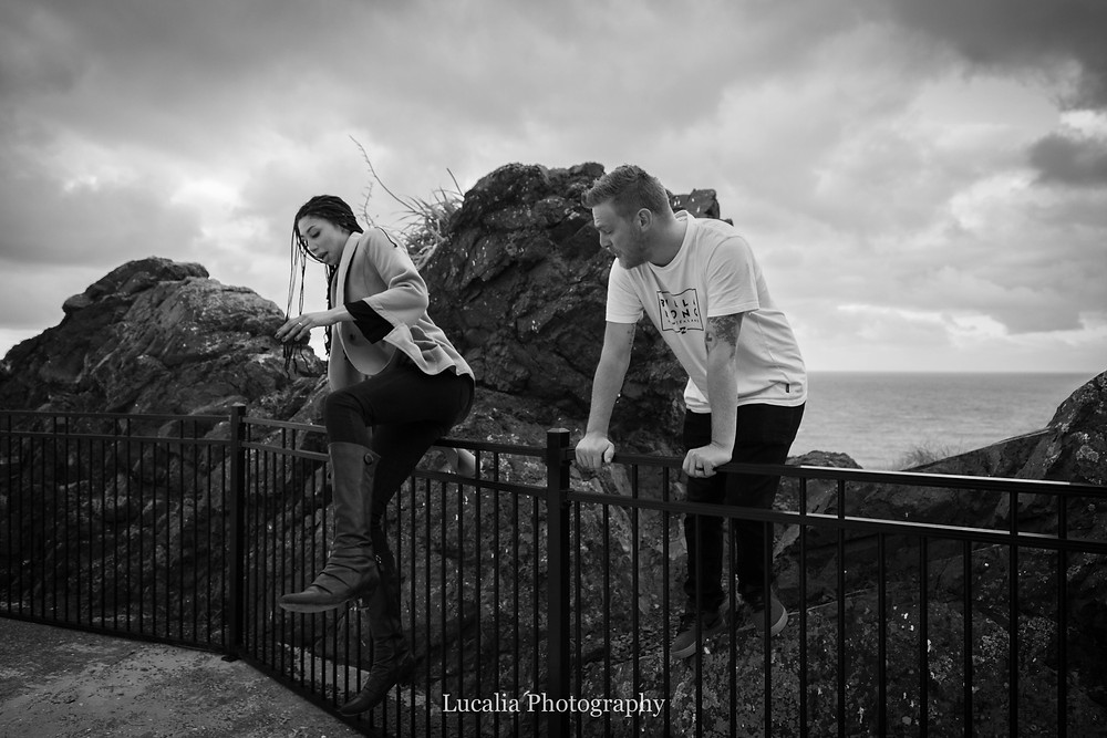 an adventerous enaged couple jumping a fence overlooking the ocean, Cape Palliser, Wairarapa