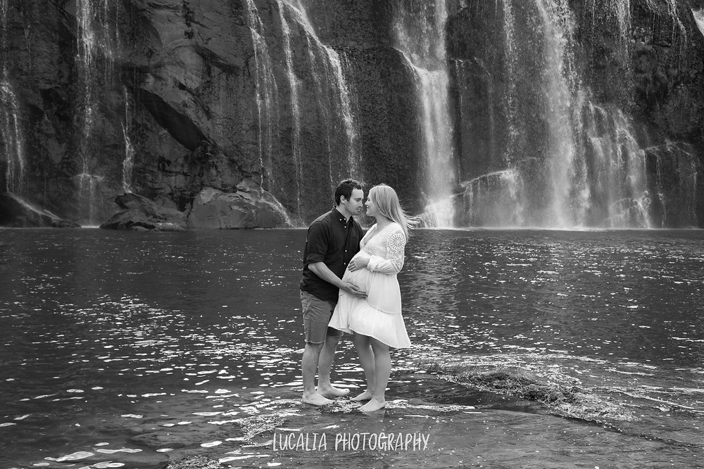 male kissing his pregnant partner with waterfall in background, Wahi Falls, Tararua, Lucalia Photography