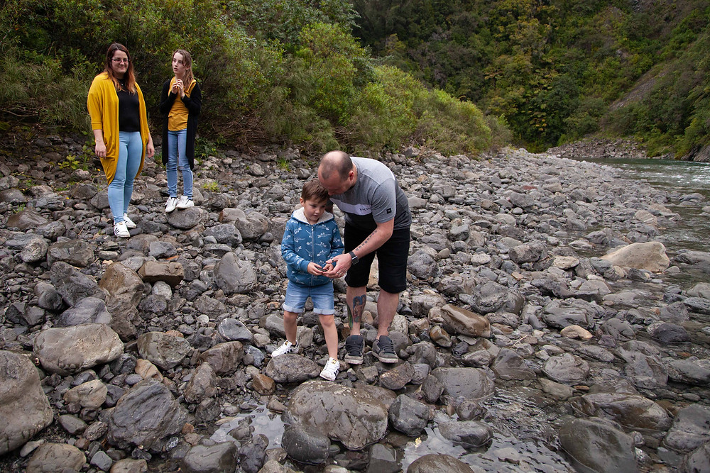 mum and daughter watching dad and son on river bank Waiohine Gorge, Wairarapa family photographer