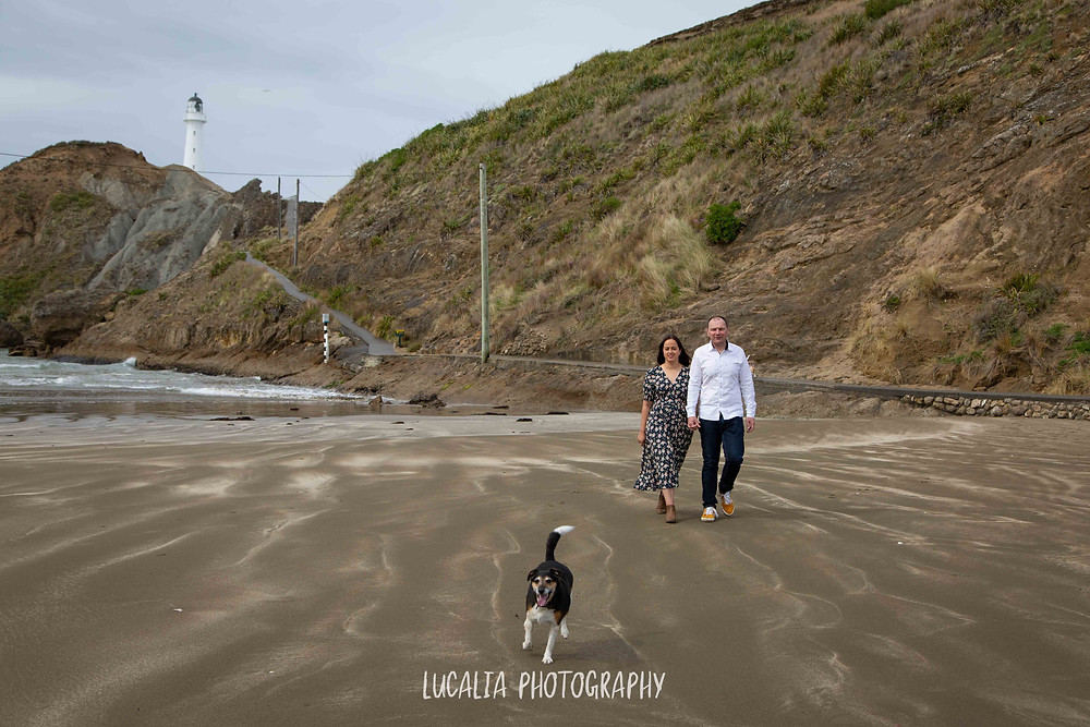 engaged couple walking along the beach with their dog and Castlepoint lighthouse in the background, Lucalia Photography Wairarapa wedding photographer