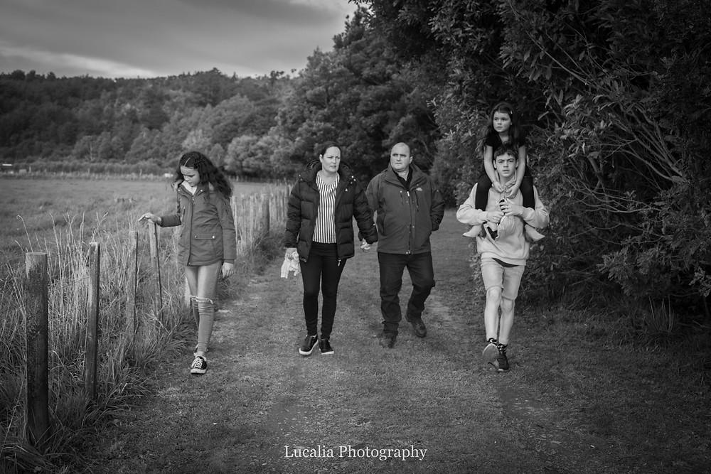 family walking along fenceline towards camera, Wairarapa family photographer