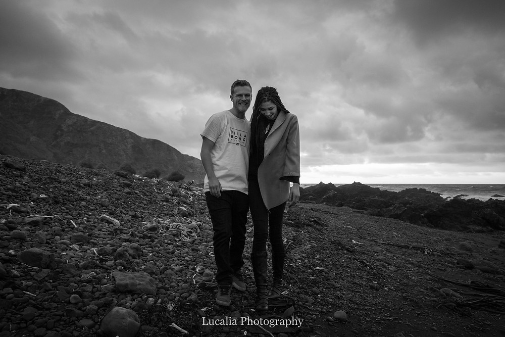 full length black and white portrait of an engaged couple at sunrise at Cape Palliser, Wairarapa