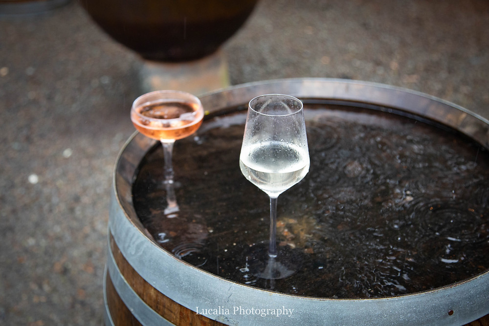 wine glasses on a wine barrel outside in the rain at Rose & Smith at Tauherenikau Wairarapa wedding venue