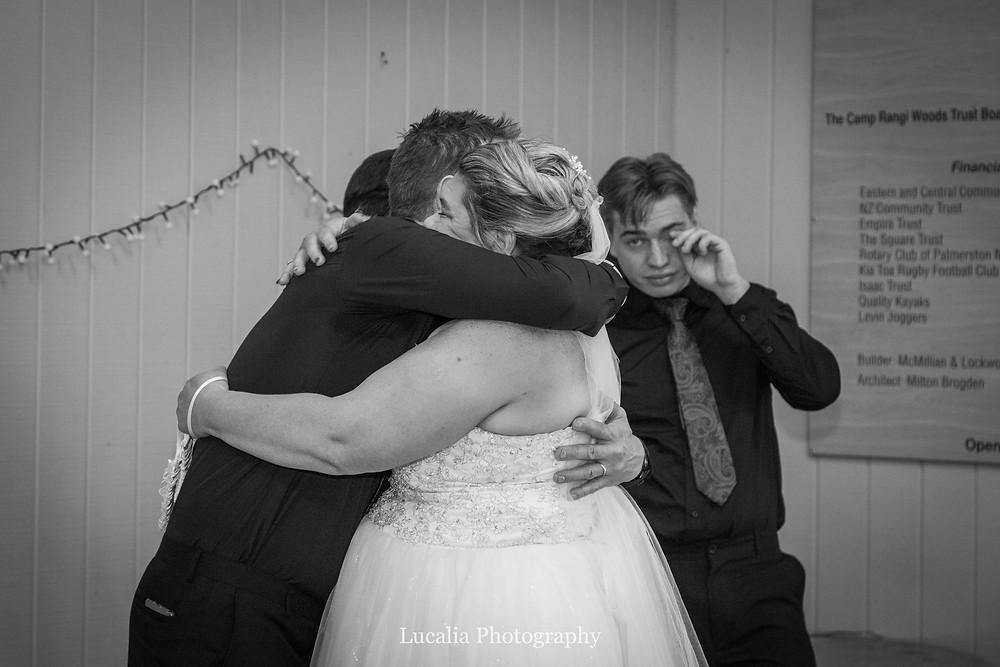 bride hugs groomsman with emotional son in background, Wairarapa wedding photographer