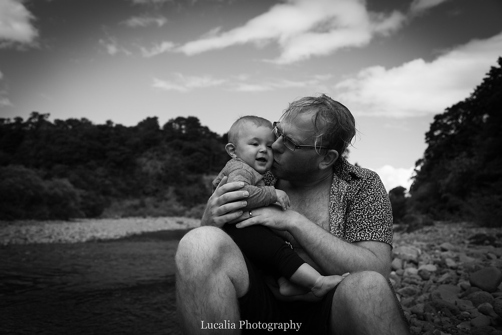 dad sitting nex to a river kissing his 6 month old son Tararua Forest Park, Wairarapa family photographer