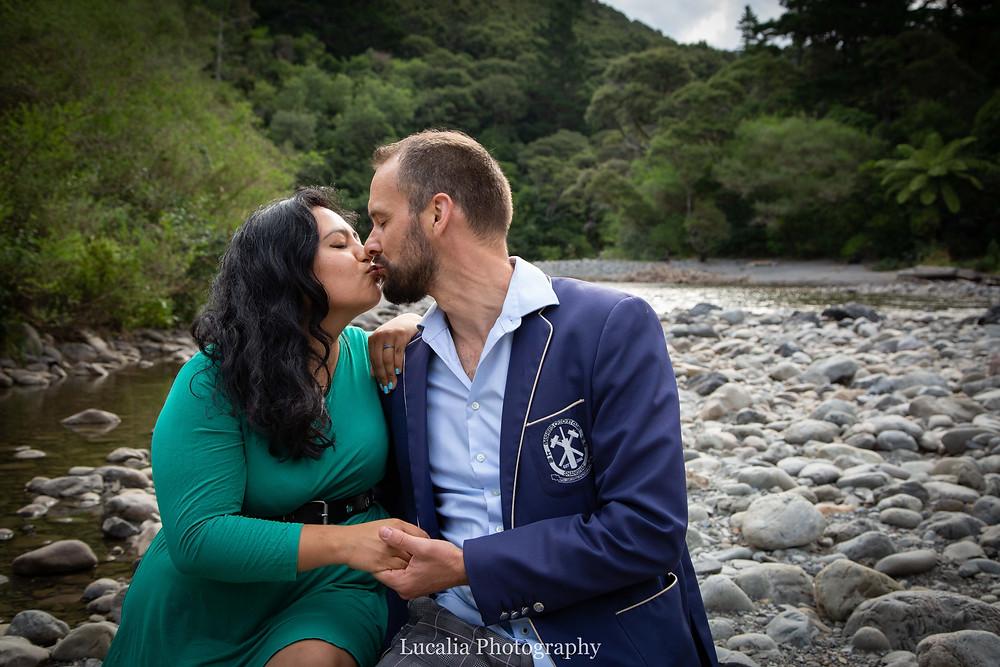 engaged couple sitting down kissing next to a river, Wairarapa