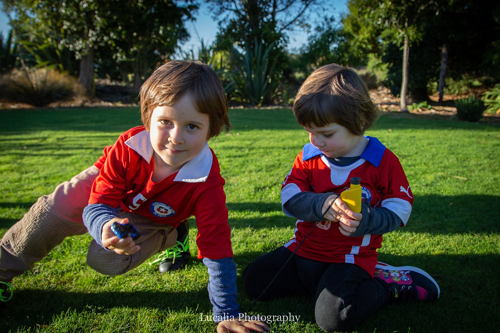 two boys playing with toys outside on the grass, Wairarapa family photographer