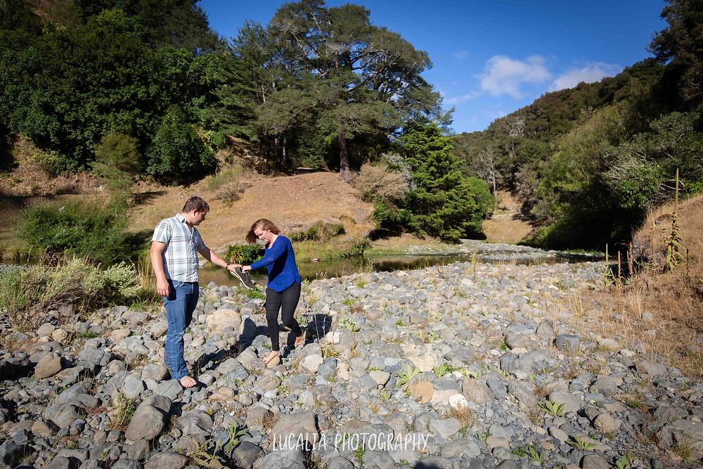 husband to be helping his bride to be walk across river rocks, Martinborough Wairarapa wedding photographer
