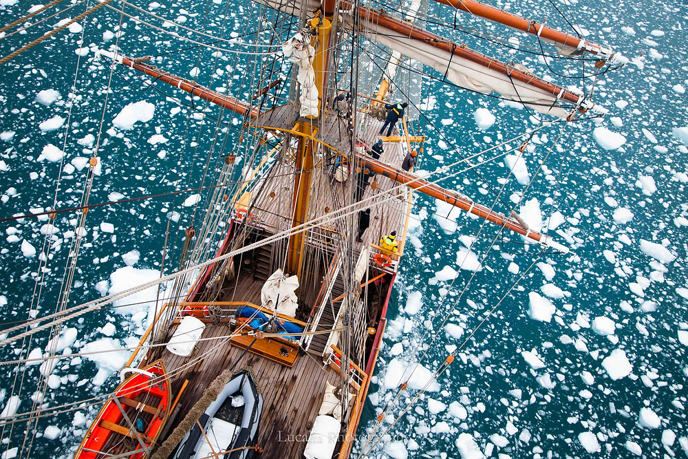 A photograph taken from the rigging of the tall ship Europa, looking down at the deck of the ship. There are chunks of ice floating in the sea.