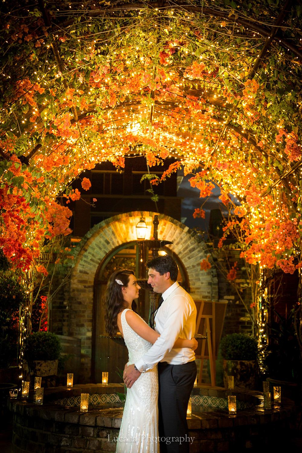 bride and groom looking into each other's eyes underneath pink flower and fairy light arch