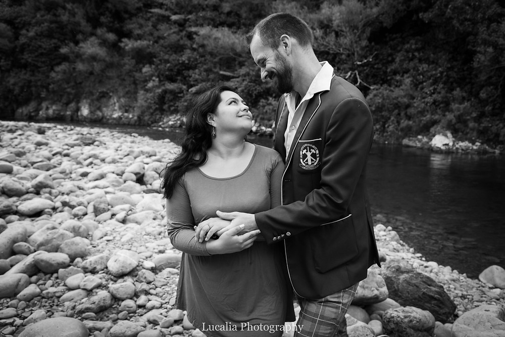 engaged couple looking at each other standing next to the Tauherenikau River, Wairarapa