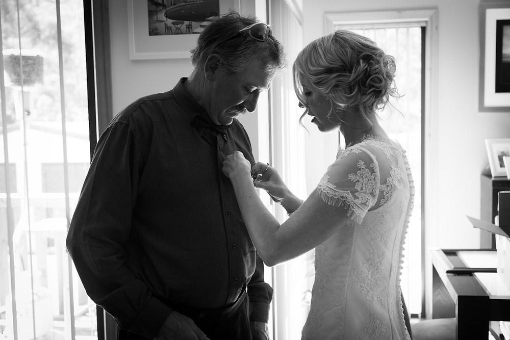 bride helps father of the bride tie his tie