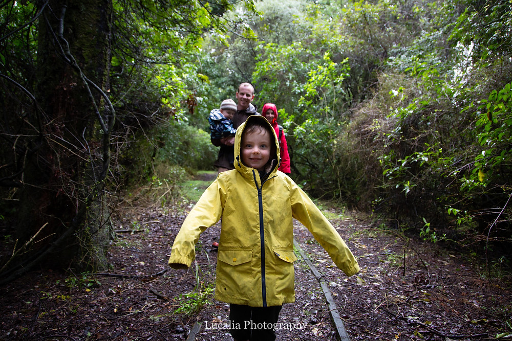 5 year old boy walking in front of his parents and brother on a wet day in the forest, Wairarapa family photographer