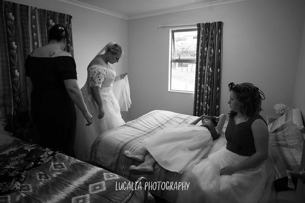 bride getting into her Astra Bridal wedding dress with flower girls, Ngawi Wairarapa wedding photographer
