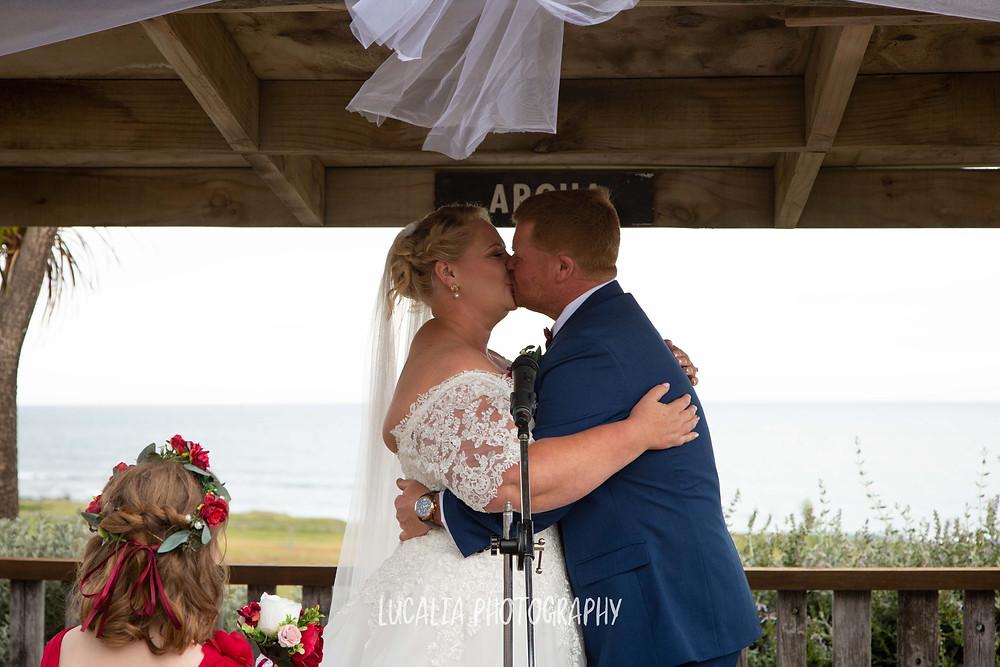 bride and groom kissing during wedding ceremony, Waimeha Camping Village, Ngawi, Wairarapa wedding