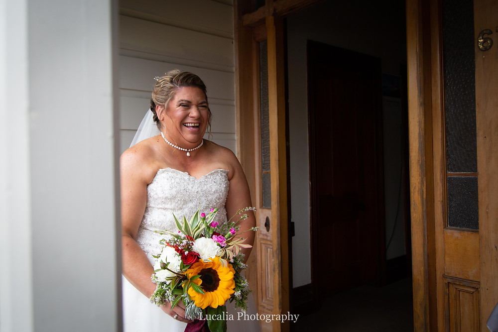 bride carrying wedding bouquet laughing outside her front door, Wairarapa wedding photographer