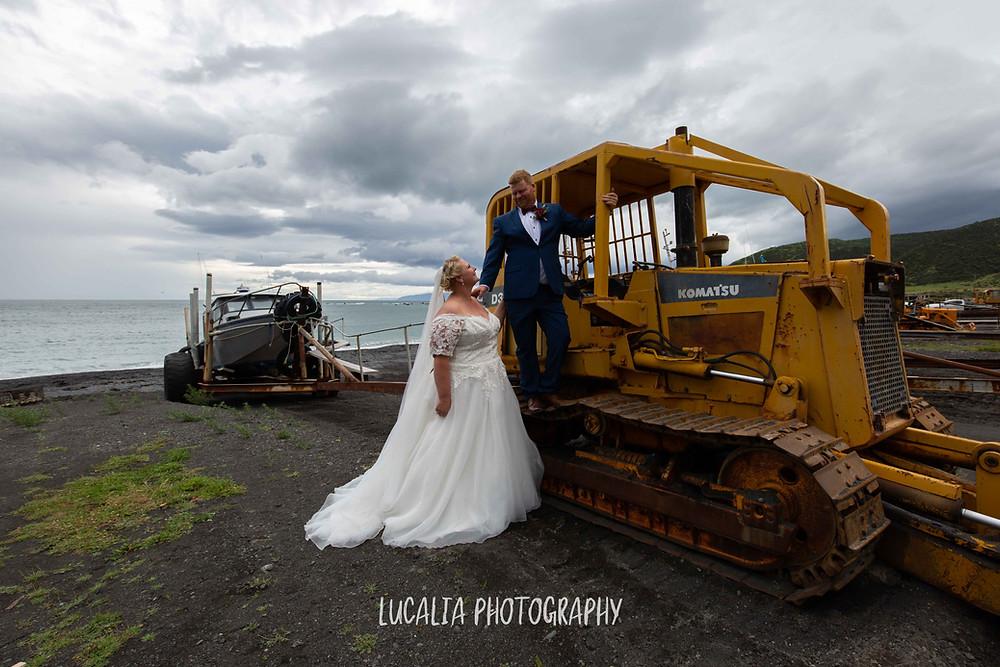 bride and groom climbing on tractor at Ngawi beach, Wairarapa wedding photographer