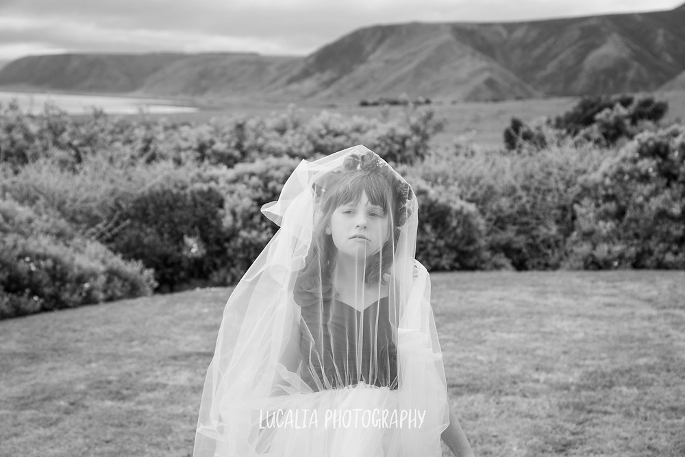 junior bridesmaid with wedding veil over her face, Waimeha Camping Village wedding venue, Ngawi, Wairarapa wedding