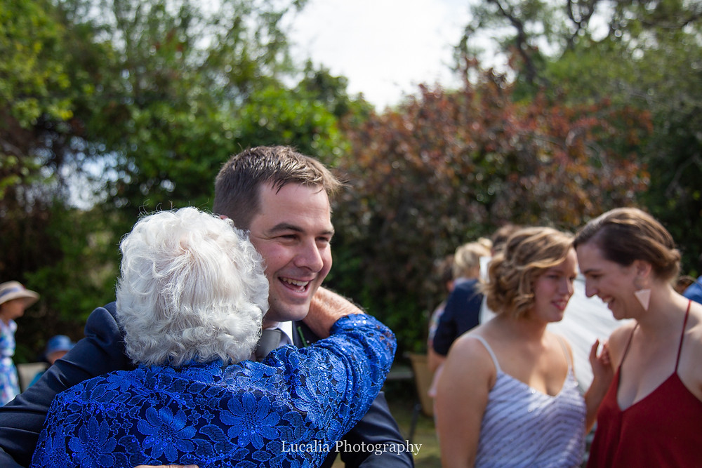 groom being hugged by grandmother with bride and bridesmaid in background, Wairarapa wedding photographers
