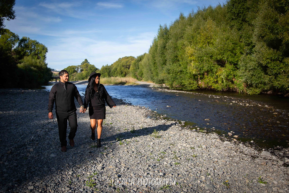 engaged couple walkng next to a river, Henley Lake, Wairarapa wedding photographer