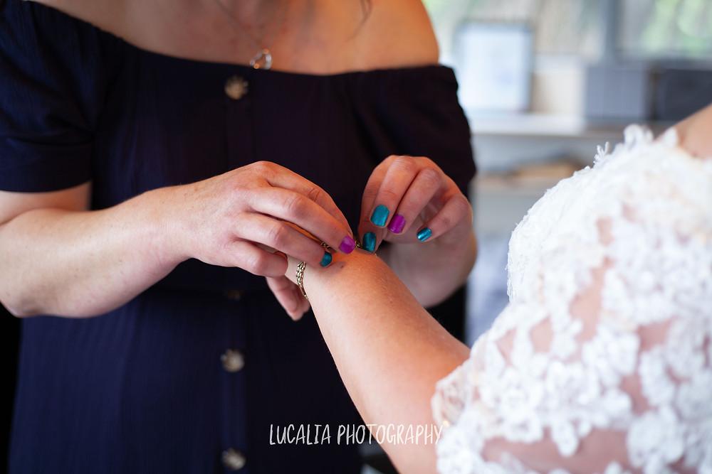 friend helping bride put on bracelet, Ngawi Wairarapa wedding photographer