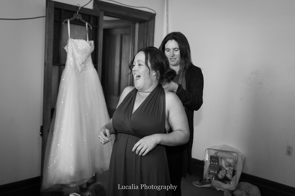bridesmaide laughing having infinity dress tied up with wedding dress in the background, Wairarapa wedding photographer