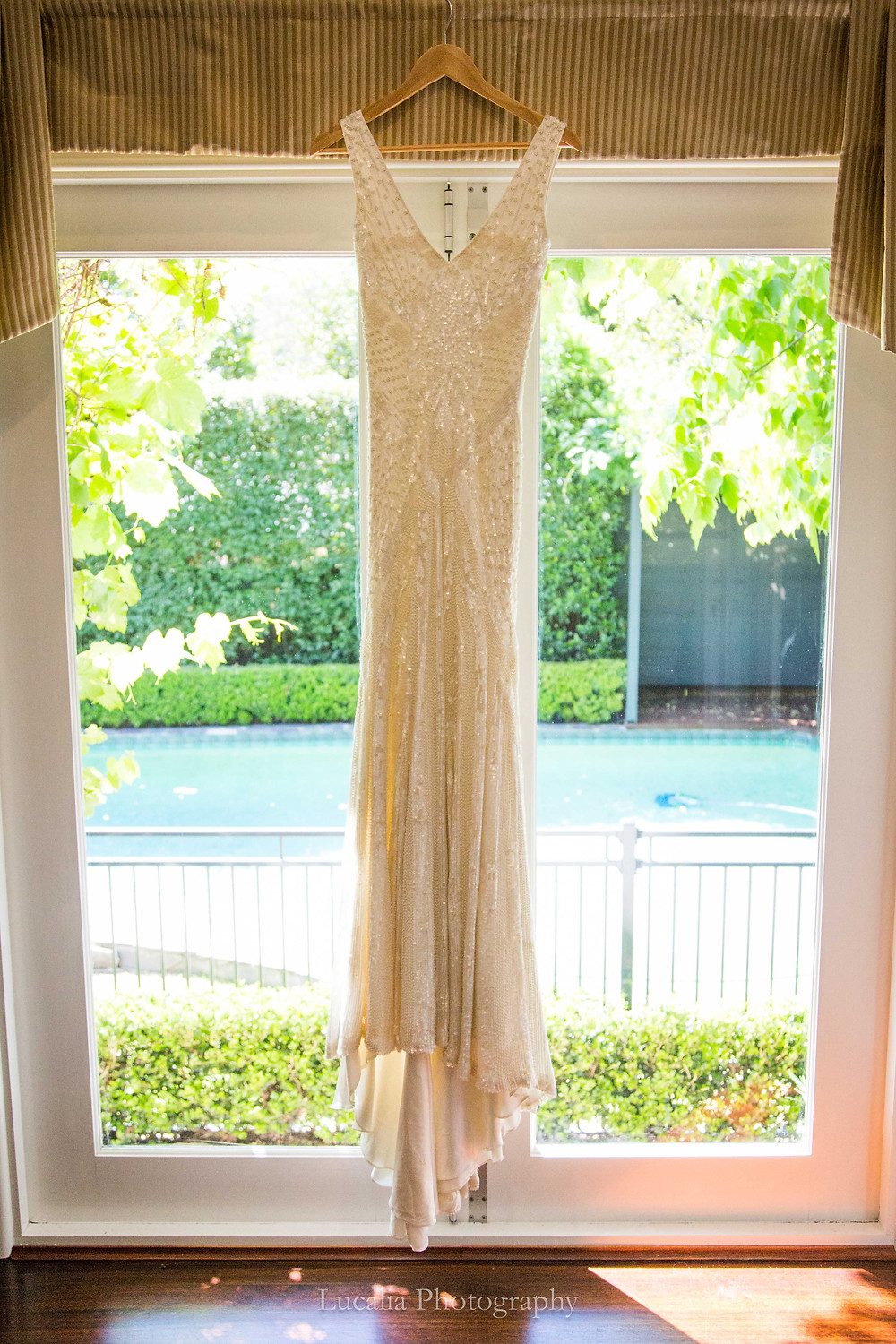 Karen Willis Holmes wedding dress hanging in a window with leaves in the background