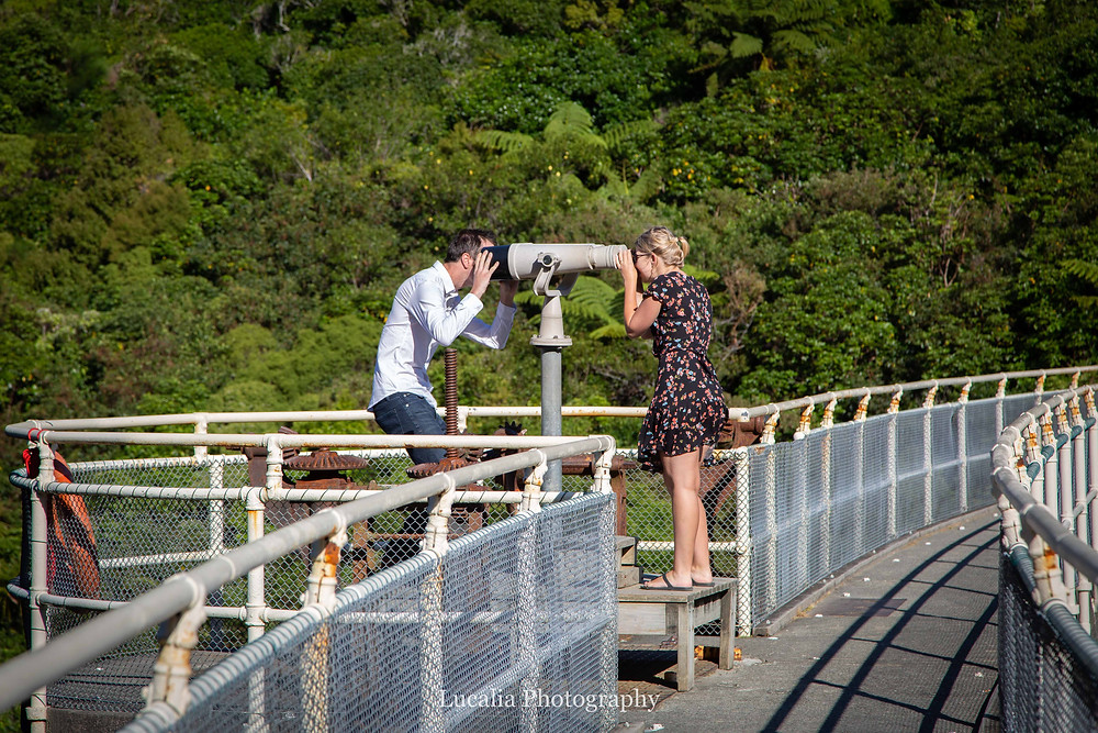 engaged couple having fun both looking through opposite ends of a telescope, Zealandia, Wellington