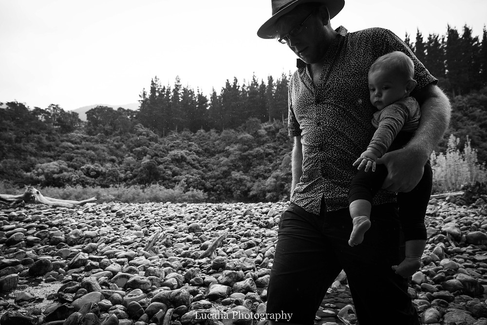 dad carrying 6 month old baby on the rocky bank of a river, Tararua Forest Park, Wairarapa family photographer