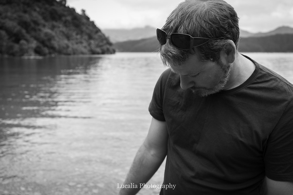 husband with sunglasses on his head looks down at the bay, Wairarapa photographer
