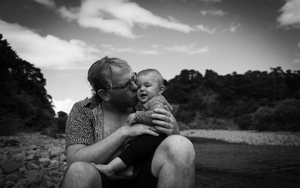 dad kissing baby near a river, Wairarapa family photographer what to wear