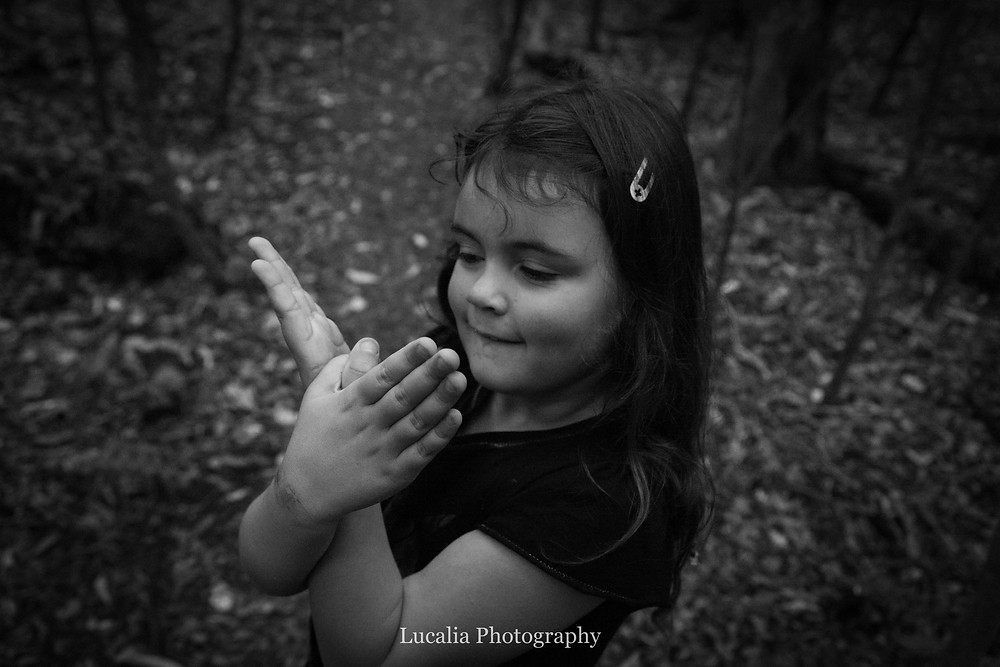 little girl making a butterfly with her hands in a forest, Wairarapa family photographer