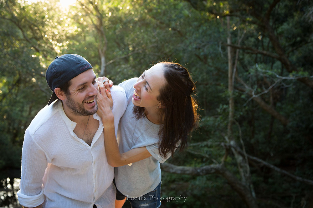 an engaged couple laugh together in the bush sunset, Wairarapa