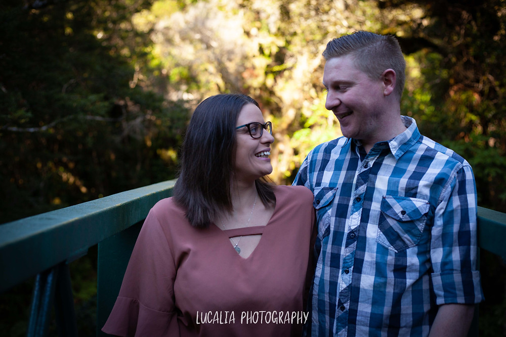 engaged couple looking at each other smiling on a bridge, Mt Holdsworth, Wairarapa wedding photographer