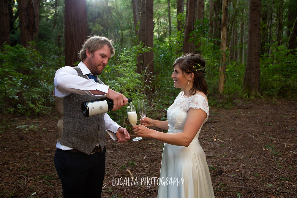 groom pouring Le Gra sparkling wine for his bride in a forest, Kiriwhakapapa Wairarapa wedding photographer