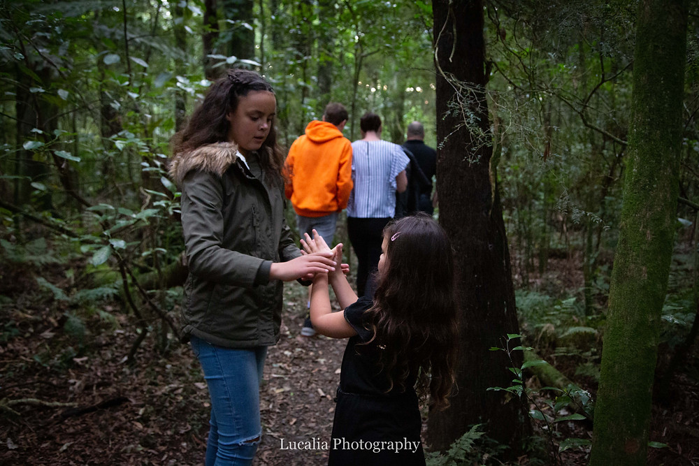 older sister showing younger sister how to make a butterfly with her hands in a forest, Wairarapa family photographer