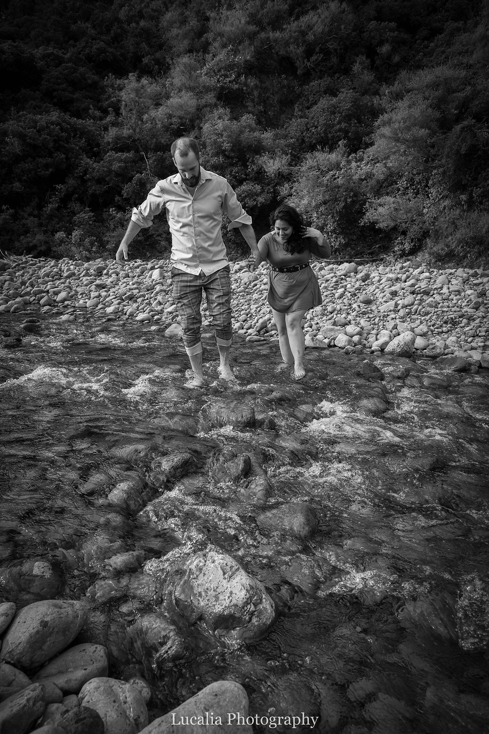 engaged couple walking over stones in a river, Wairarapa