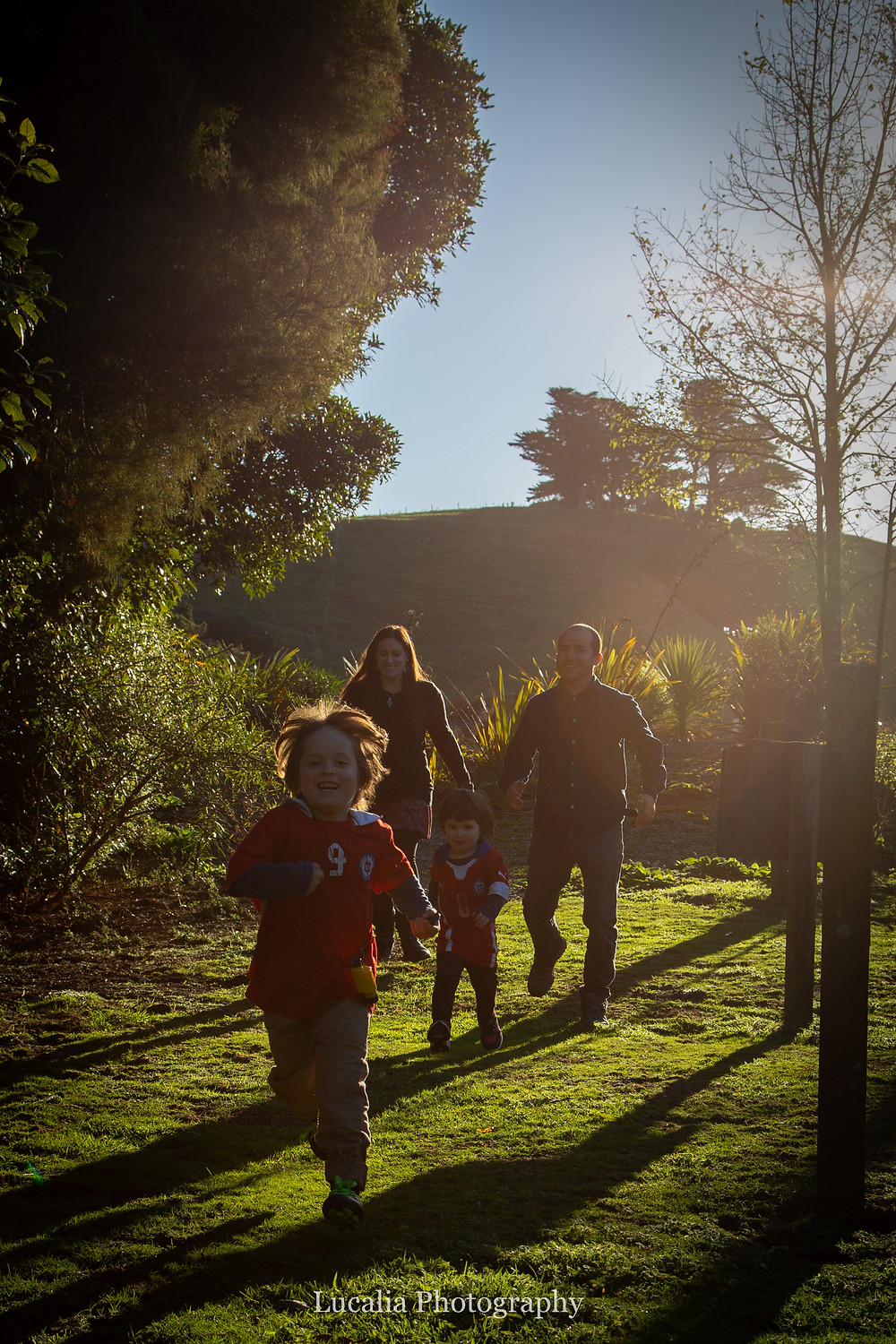 family running down a grassy hill in golden light, Wairarapa family photographer