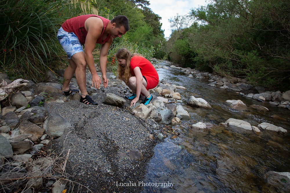 engaged couple uncovering stones on the side of a river, Featherston Wairarapa