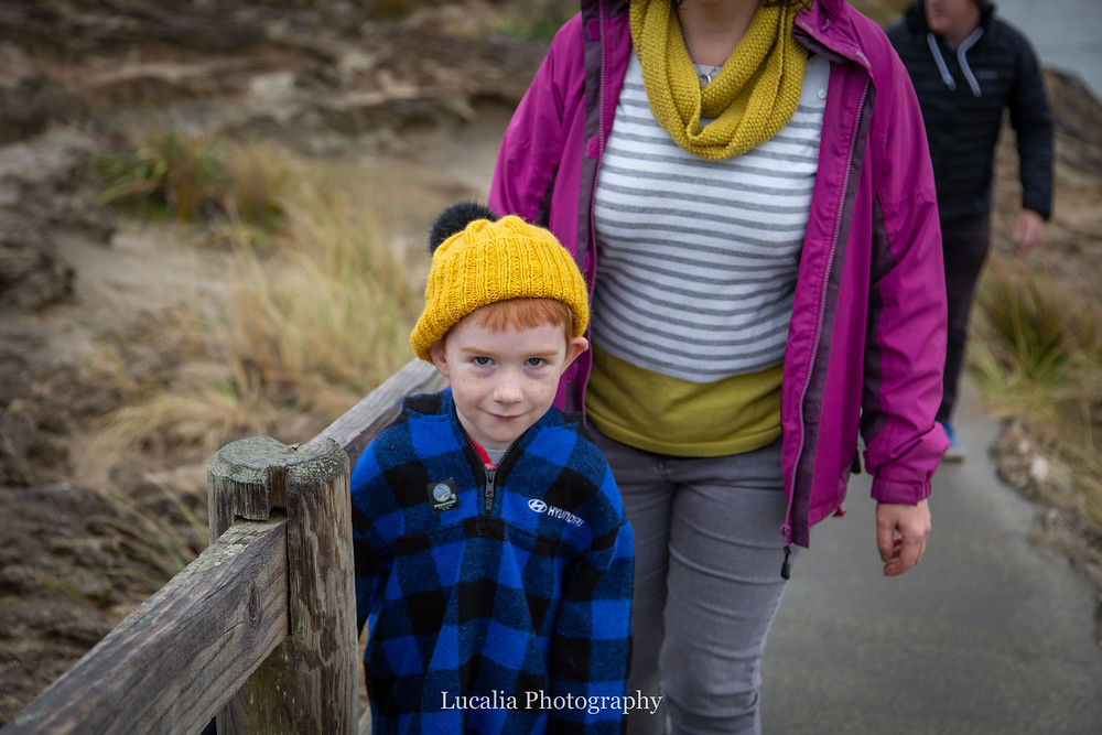 boy looking at the camera wearing a yellow beanie with his mum behind him, Castlepoint Wairarapa family photographer