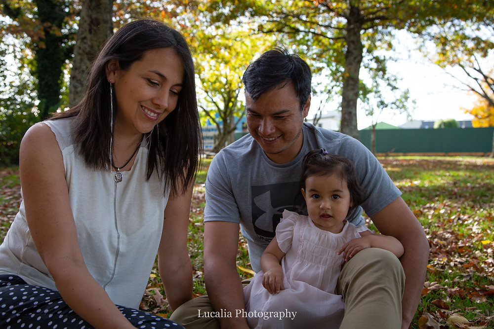 mum dad and daughter sitting in a park with autumn leaves, Wairarapa family photographer what to wear